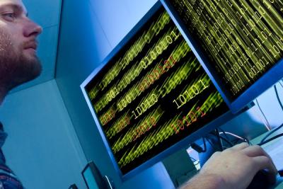 Onderzoeker bekijkt computerdata op schermen