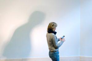Schaduw kijkt over schouder van vrouw mee naar invoer op telefoon.