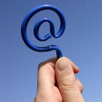 Hand houdt e-mail teken (apenstaartje) vast