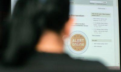 Vrouw achter beeldscherm bekijkt website Alert Online