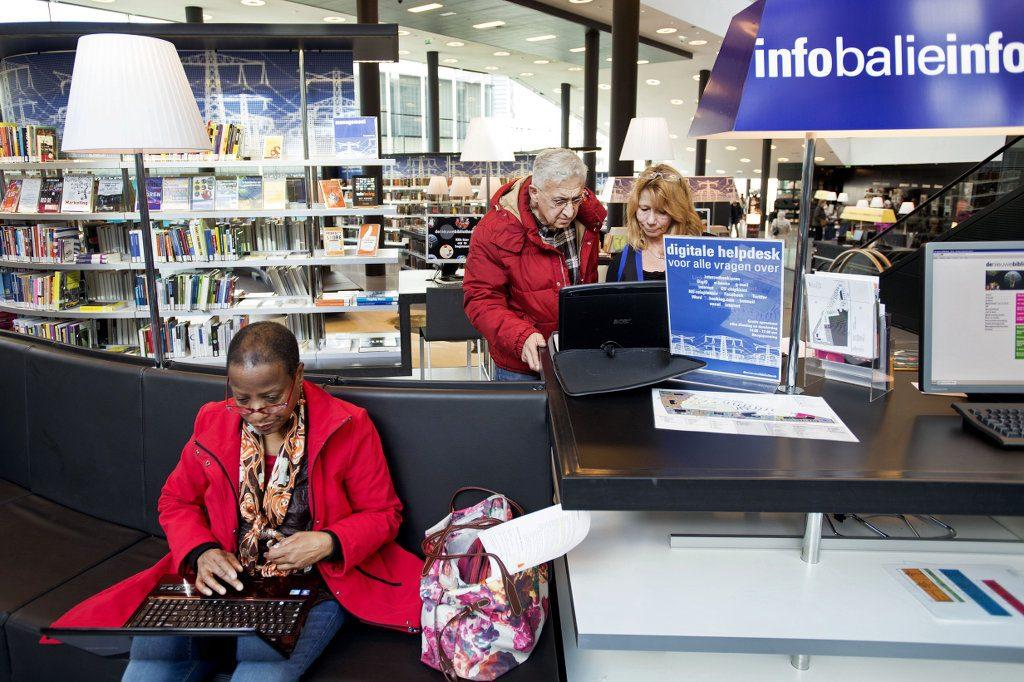 Mensen bezoeken digitale helpdesk bij informatiebalie