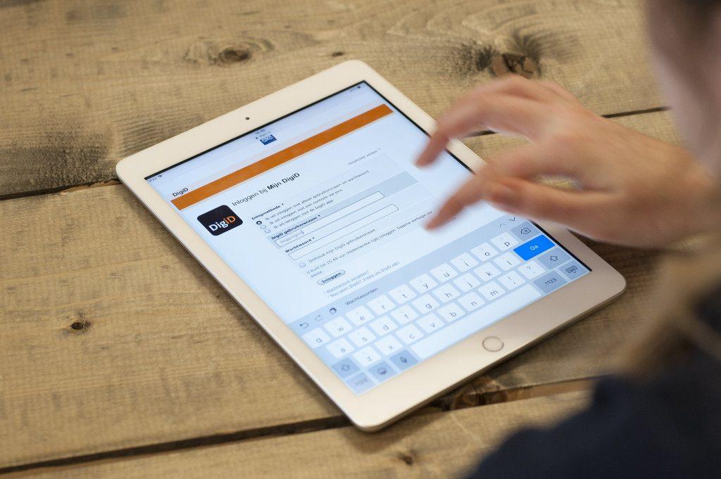 Iemand logt via tablet in op DigiD.