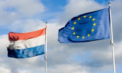 De vlag van Europa en de Nederlandse vlag wapperend in de wind