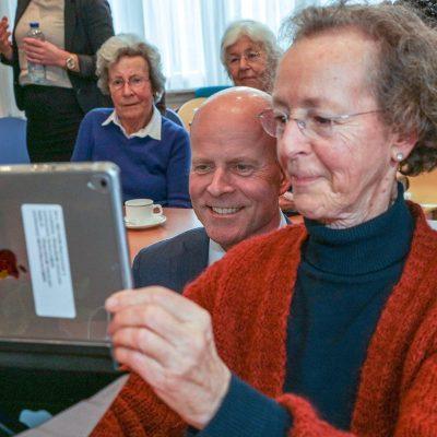 Raymond Knops kijkt samen met senioten naar een iPad