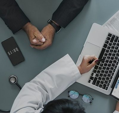 Decoratief: specialist en patiënt met gegevens op laptop