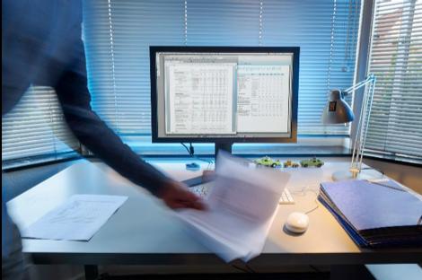 Persoon pakt stapel papier van bureau met computer.