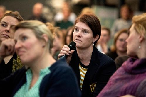 Vrouw met microfoon neemt het woord tijdens bijeenkomst.