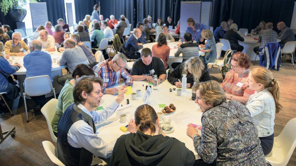Groepen mensen met elkaar in gesprek aan tafels.