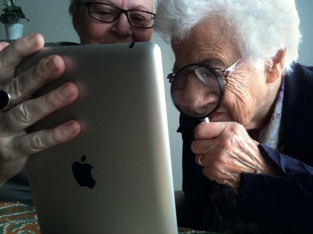Oude vrouw bekijkt met vergrootglas iPad.