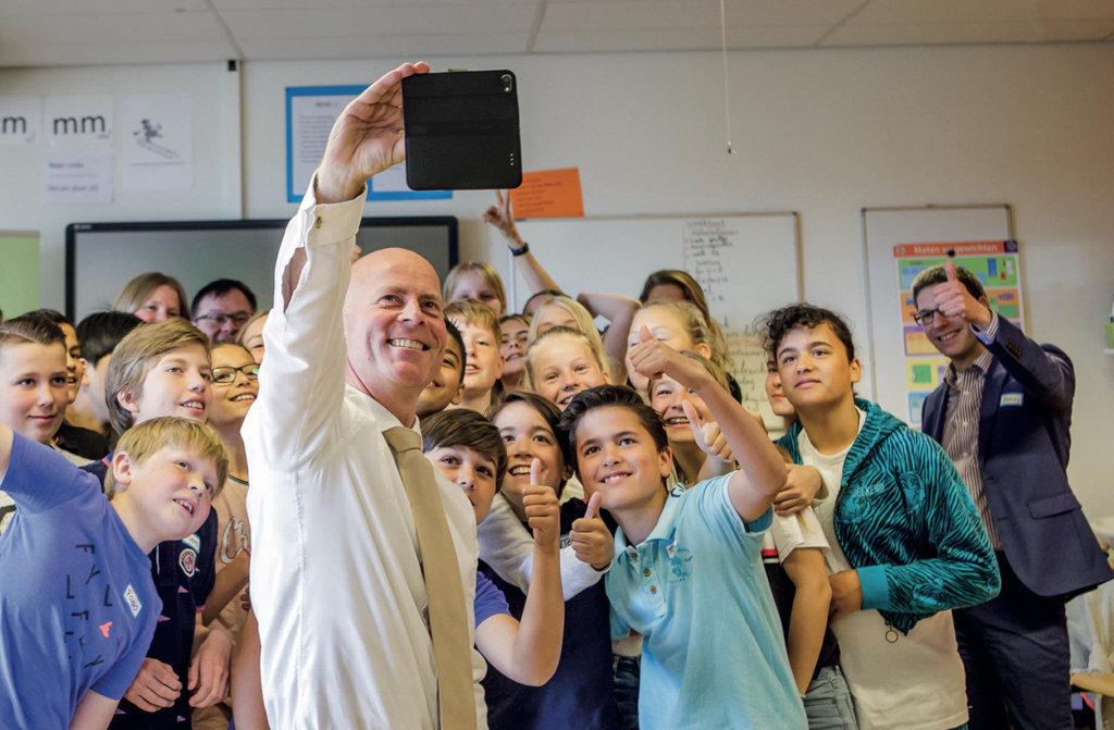 Staatssecretaris Knops maakt selfie met schoolklas.