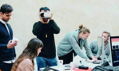 vijf jonge mensen rond een tafel met computers. Een ervan draagt een virtual-reality-bril; een ander werkt op een laptop; een meisje is bezig op een tablet
