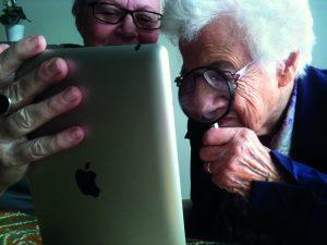 Twee oudere vrouwen bekijken een ipad; een ervan gebruikt een vergrootglas