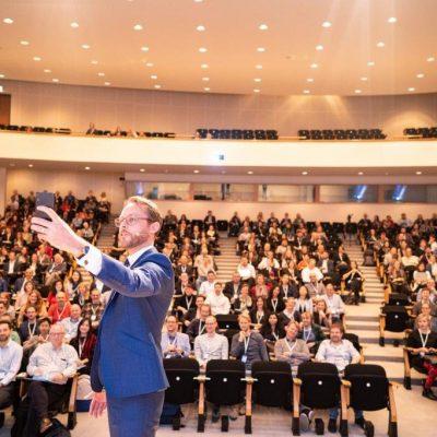 Persoon maakt selfie met zaal op congres