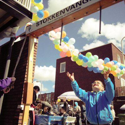 Foto van een buurtfeest, kind houd slinger omhoog.