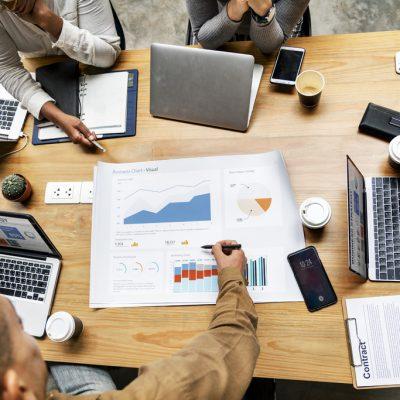 Foto van een tafel met mensen die bezig zijn data te analyseren op hun computers, laptops en tablets.