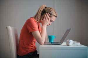Vrouw kijkt gefrustreerd naar laptop
